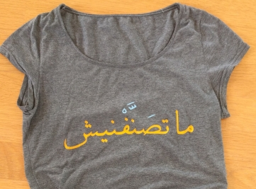zu sehen ist ein graues T-Shirt mit gelber arabischer Schrift.
